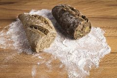 Small whole grain bread stick with freshly made walnuts. Small bar of wholemeal bread with freshly made walnuts next to some ingredients on a wooden table stock photos