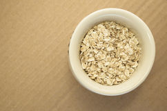 Small wholemeal oat flakes in a white  cup Stock Images