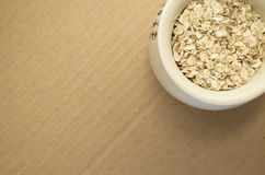 Small wholemeal oat flakes in a white porcelain cup Royalty Free Stock Photos