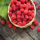 Small wicker basket with fresh ripe raspberries. On a wooden background Royalty Free Stock Image
