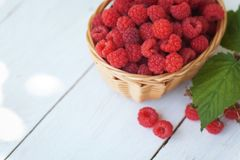 Small wicker basket with fresh ripe raspberries stock photo