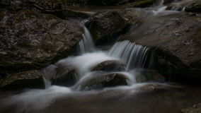 A small wild stream flows over rocks in time lapse stock video footage