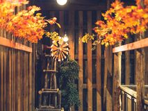 Small wind turbine for decoration in wooden house with autumn leaves. stock photography