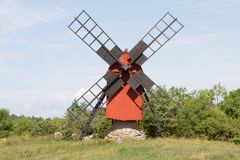 Small red Windmill. A small windmill stands on a stone pile Royalty Free Stock Photography