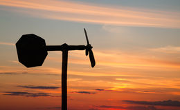 Small windmill style weather vane silhouette Stock Photo