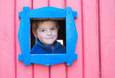 Small window. A boy looking through small window Stock Images