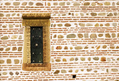 Small window on ancient wall. Small, narrow window on the side of a decorative and ancient stone wall Royalty Free Stock Images