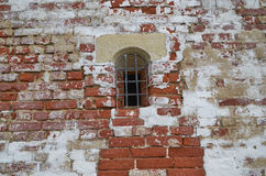 Small window with bars in the tower of the fortress wall. The image of a small window with bars in the tower of the fortress wall Savvino-Storozhevsky monastery Stock Photo
