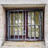 Small window from the basement behind the bars stock photo