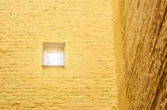 A small window in the brick wall. Corner of the house. Concept minimalism. A small window in the brick wall. Corner of the house. Concept minimalism Royalty Free Stock Photography