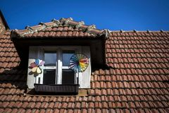 A small window decorated with windbreaks in the red roof Stock Image