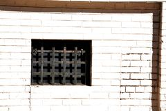 Window with metal grate. A small window in an old brick building with a heavy metal grate covering it Stock Photography