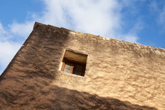 Small window in old stone wall, under blue sky Royalty Free Stock Photography