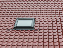 Small window in tiled red roof Royalty Free Stock Photo