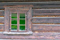 A small window in the wall of an old wooden house stock photos