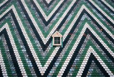 Small window on on wall painted zigzag. Vienna, Austria. Small window on on the wall painted with blue, green and white stripes in zigzag. St. Stephen`s stock image