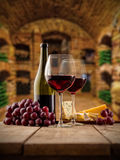 Small wine cellar with two glasses and botte of wine. Small and old wine cellar with two glasses and bottle of red wine, served with grapes and cheese on wooden Stock Image