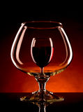 Small wineglass is visible through a large glass of wine. Image of small wineglass is visible through a large glass of wine on dark orange background Royalty Free Stock Image