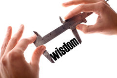 Small wisdom. Color horizontal shot of two hands holding a caliper and measuring the word wisdom royalty free stock photography