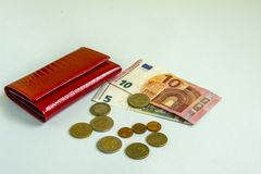 Small woman red wallet. Banknotes of 5 and 10 euros. Some coins. Blue background. Small woman red wallet. Banknotes of 5 and 10 euros. Some coins stock photography