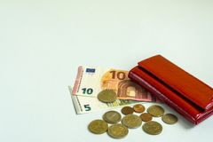 Small woman red wallet. Banknotes of 5 and 10 euros. Some coins. Blue background. Small woman red wallet. Banknotes of 5 and 10 euros. Some coins stock images