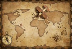 Small wood airplane over world nautical map as travel and communication concept Stock Photos