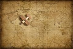 Small wood airplane over world nautical map as travel, explore and communication concept royalty free stock photo