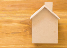Small wood house model on brown background Royalty Free Stock Images
