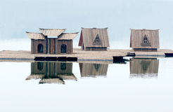 Small wood house on water. Three small wood house model on lake water and their shadow can be seen Stock Images