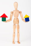 Small wood mannequin holding block house Stock Images