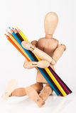 Small wood mannequin sitting with bunch of colour pencil isolate Stock Photography