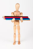 Small wood mannequin standing with bunch of colour pencil isolat Royalty Free Stock Images