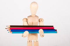 Small wood mannequin standing with colour pencil Stock Photography