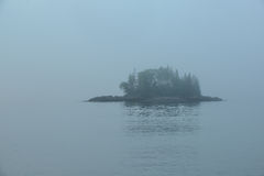 A small wooded island in the Fog Stock Images