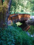 Small wooden arch bridge in a park Stock Images
