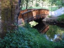 Small wooden arch bridge in a park Stock Photo