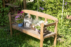Small wooden bench with flowers Royalty Free Stock Photography