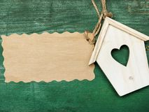 Small wooden bird house with heart decoration and blank paper. On green retro wooden background, copy space royalty free stock image