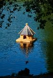Small wooden birdhouse in the middle of a lake royalty free stock images