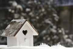 Small wooden birdhouse in snow against Christmas t Stock Image