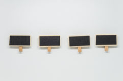 Small wooden black board clip on white background with selective focus Stock Photos