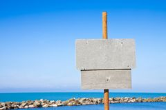Small wooden blank advertising billboard against a seascape background - image with copy space stock photography