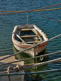 Small wooden boat. Photo of the little wooden  boat and the tangled ropes at Adriatic sea Royalty Free Stock Photo
