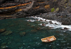 Small wooden boat anchored near rocks Royalty Free Stock Photo