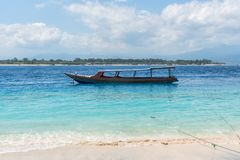 Small wooden boat on blue beach with cloudy sky and Lombok island on background. Gili Trawangan, Indonesia.  Stock Photos