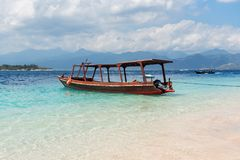 Small wooden boat on blue beach with cloudy sky and Lombok island on background. Gili Trawangan, Indonesia.  Royalty Free Stock Image