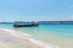 Small wooden boat on blue beach with cloudy sky and Lombok island on background. Gili Trawangan, Indonesia Royalty Free Stock Photography