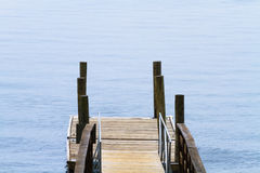 Small Wooden Boat Dock At The Lake. A single old, floating, boat dock made of wood planks and posts at the lake on an overcast day Stock Photo
