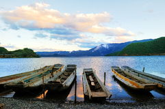 Small wooden boat in the Lugu Lake. Evening sunset, the small wooden boat while parked at the Lugu Lake Royalty Free Stock Image