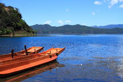 Small wooden boat in the Lugu Lake. Traditional wooden boats floating lugu lake yunnan china Royalty Free Stock Photos